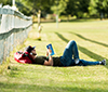 Student lying on the lawn reading a book.