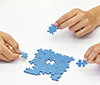 Hands laying blue puzzle pieces